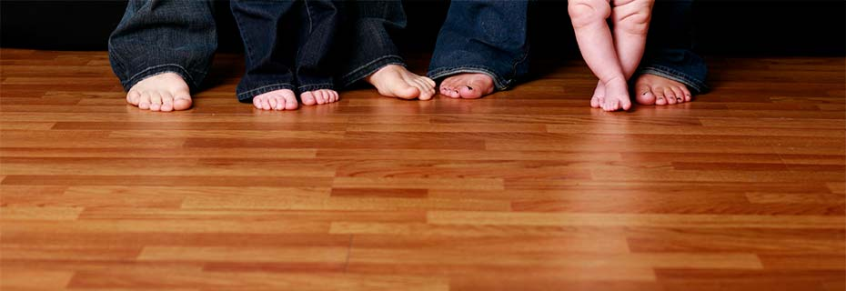 A family's bare feet on their hardwood floor