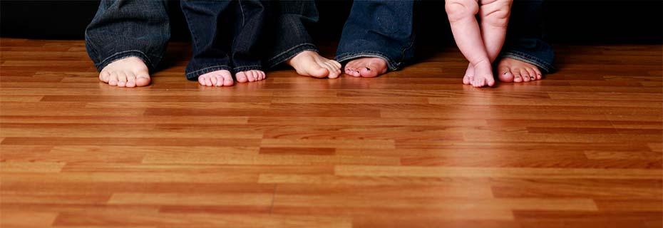 A family's bare feet on their hardwood floor