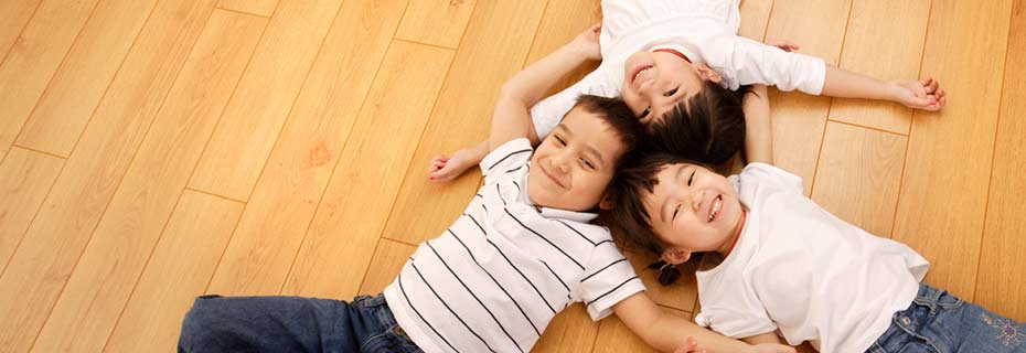 Three children play on a hardwood floor