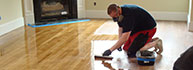 An craftsman refinishes a floor